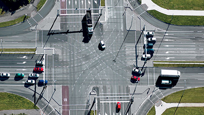 Aerial view of vehicles accelerating through an intersection